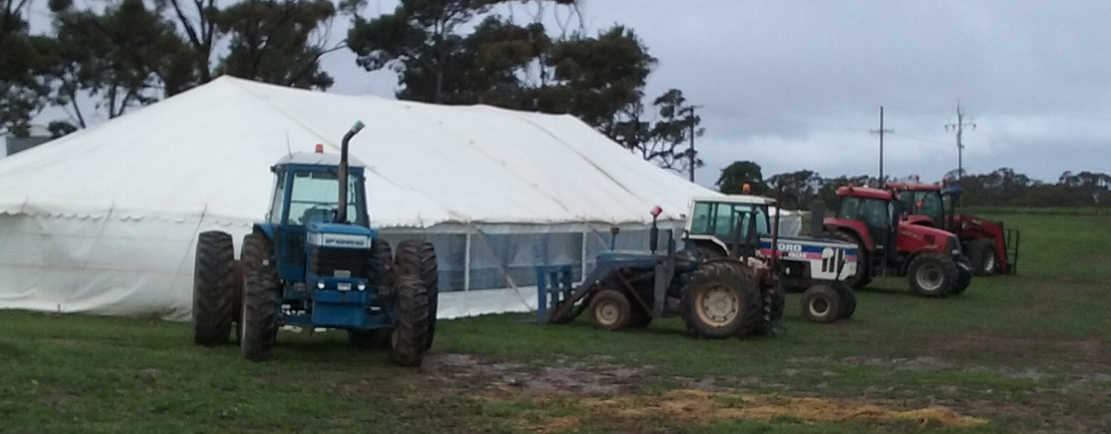 Tractors holding down tent at sale